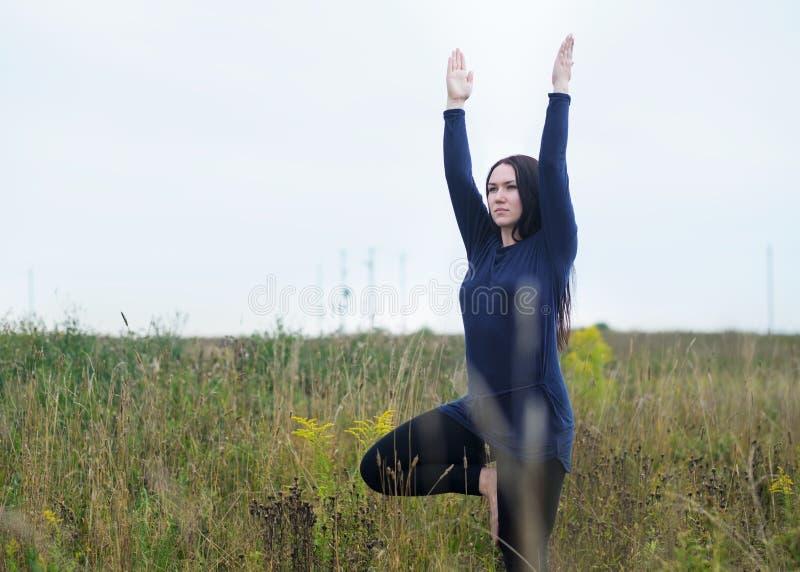 De jonge Europese vrouw in blauwe t-shirt die zich in yoga bevinden stelt op het gras in het park royalty-vrije stock afbeelding