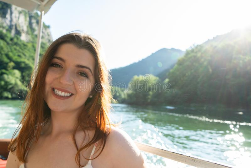 De jonge Europese vrouw is roeien op een meer Meisje die tonend tanden, die in kleine boot bij zonsondergang op de rivier in zitt royalty-vrije stock afbeelding