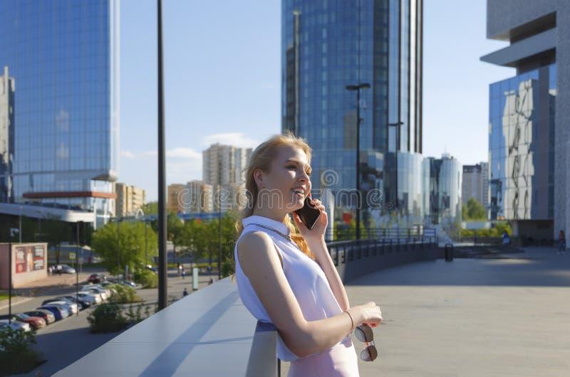 De jonge Europese vrouw status op stadsstraat leunde terug tegen verschansing en sprekende telefoon stock foto's