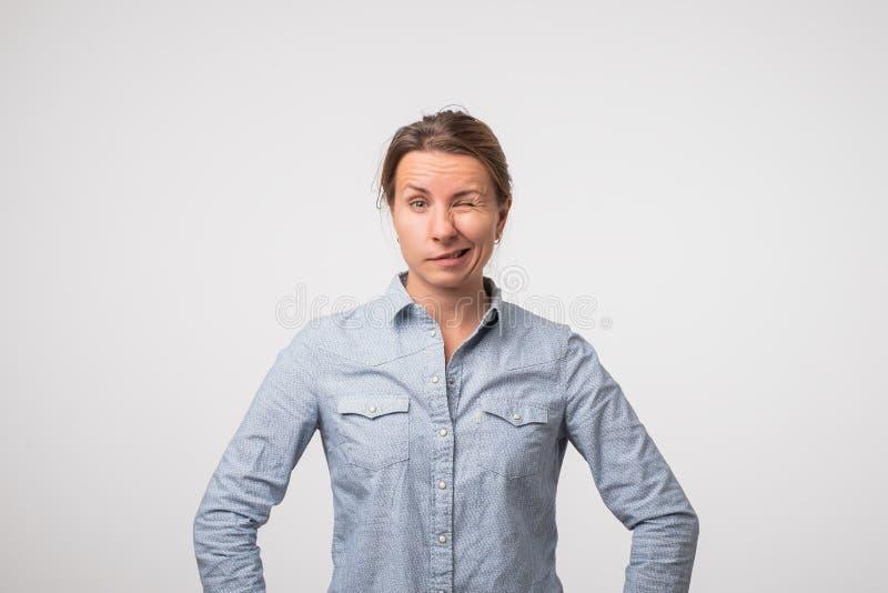 De jonge Europese vrouw in t-shirt knipoogt naar de camera Zij is gelukkig stock fotografie