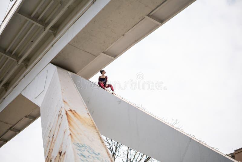 De jonge extremal onverschrokken vrouw beklimt omhoog onder de brug en het hebben van pret Gevaarlijke trucs en het riskeren zond stock foto
