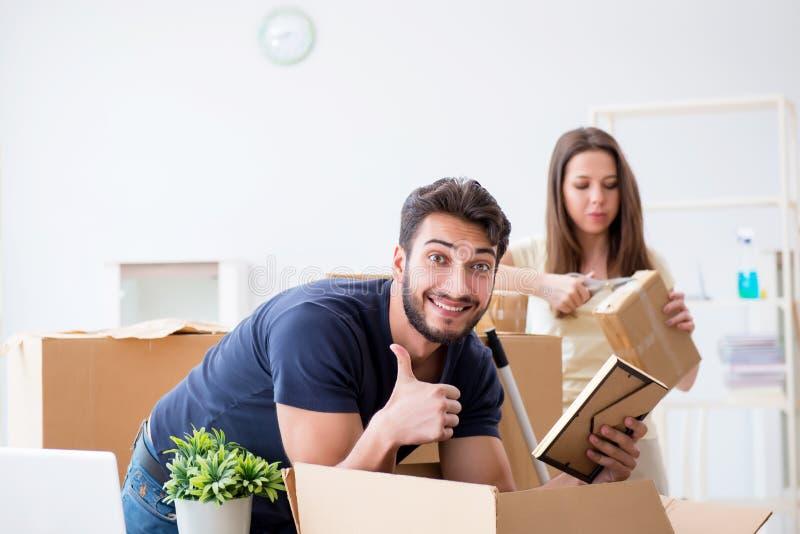 De jonge familie die bij nieuw huis met dozen uitpakken stock afbeelding