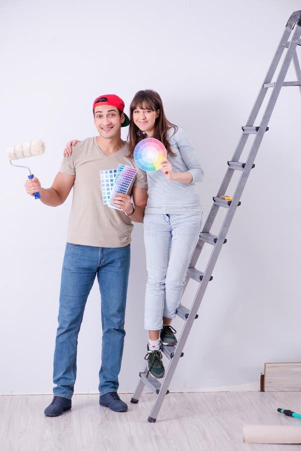 De jonge familie die vernieuwing doen thuis - het schilderen muren royalty-vrije stock foto's