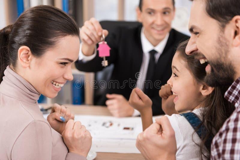 De jonge familie is gelukkig om nieuw huis in bureau van makelaar in onroerend goed te kopen Kopend huis Huis voor Verkoop stock afbeeldingen