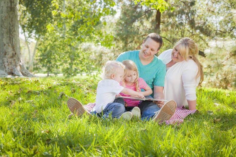 Download De Jonge Familie Geniet Van Lezend Een Boek In Het Park Stock Foto - Afbeelding bestaande uit mannetje, moeder: 39115536