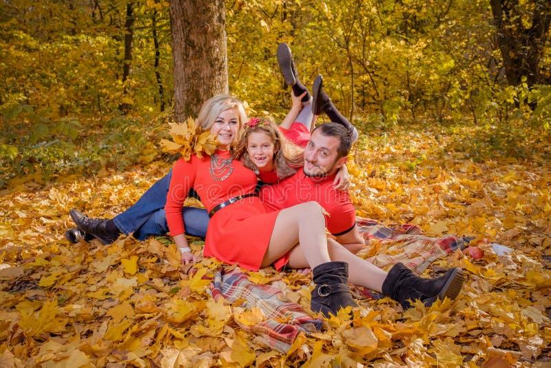 De jonge familie heeft pret op plaid in zonnige warme de herfstdag stock foto's