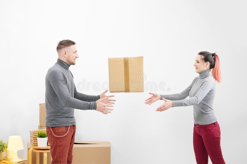 De jonge familie, de man en de vrouw in nieuwe flats werpen elkaar een doos Dozen met lading op een witte achtergrond stock afbeeldingen