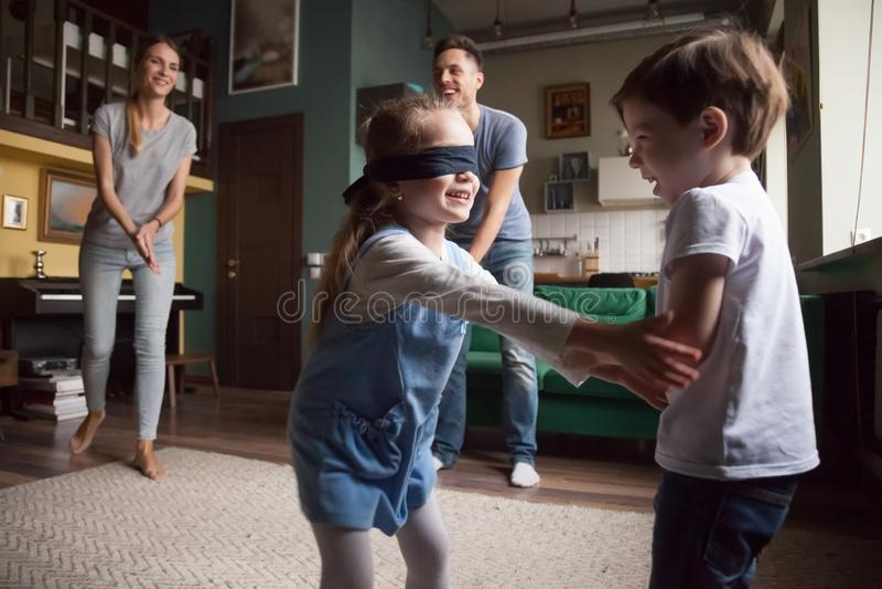 De jonge familie met twee kinderen het spelen huid-en-zoekt royalty-vrije stock foto's