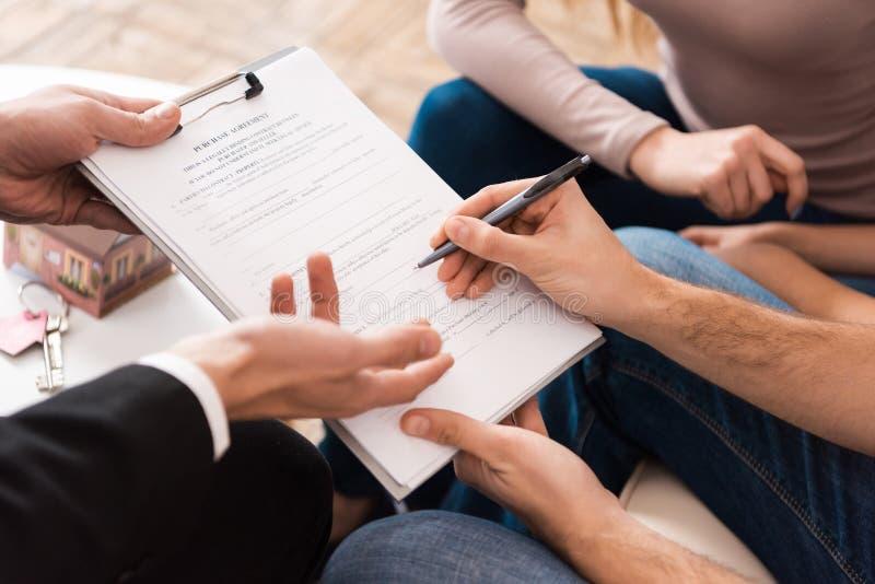 De jonge familie ondertekent partnerovereenkomst om nieuw huis samen met makelaar in onroerend goed te kopen royalty-vrije stock afbeelding