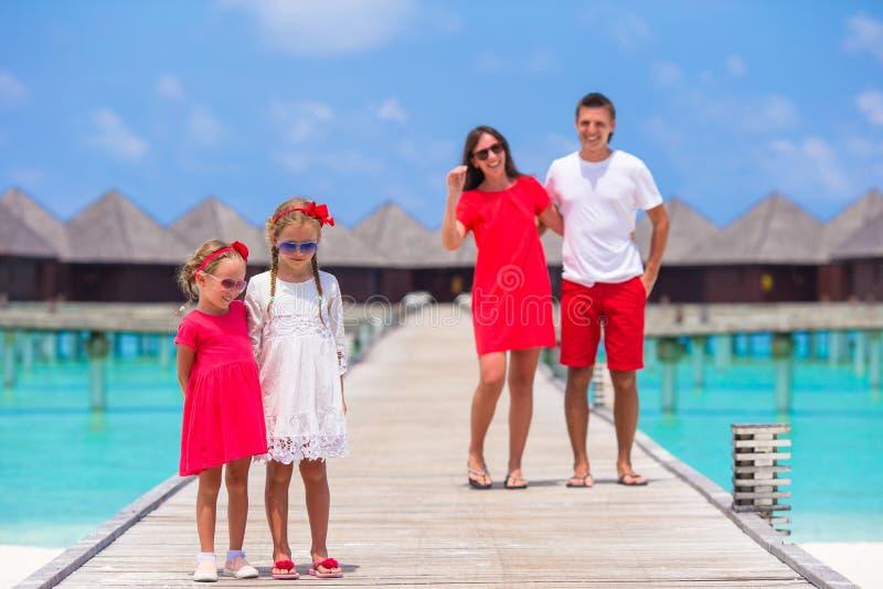 De jonge familie van vier heeft pret op houten pier stock afbeelding