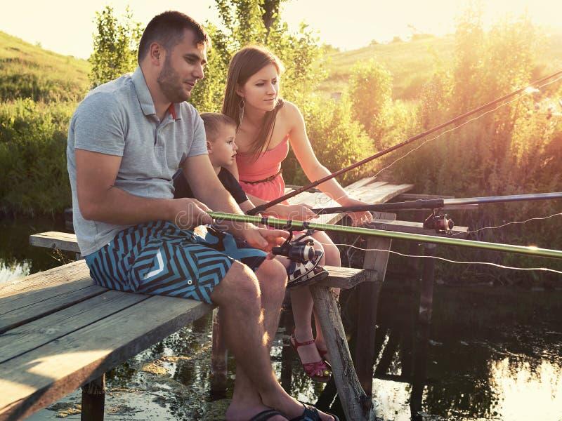 De jonge familie visserijvakantie met houten planked voetpad stock afbeelding