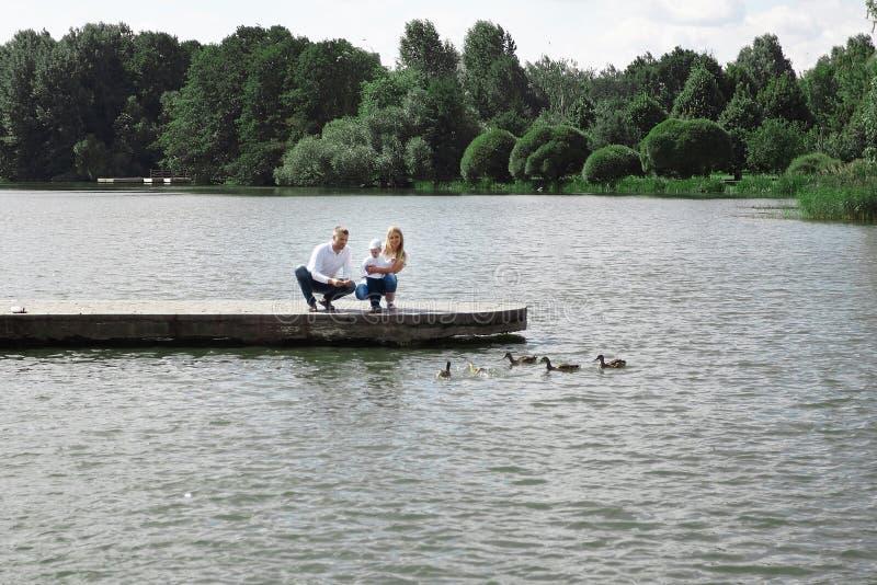 De jonge familie voedt wilde eenden zittend op een pijler door het meer royalty-vrije stock fotografie