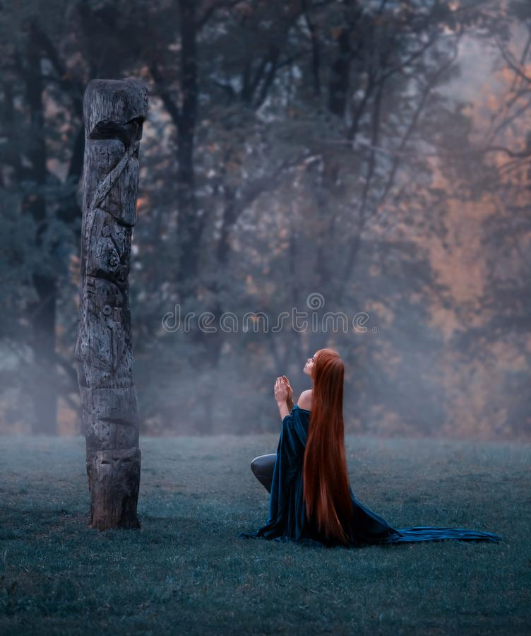 De jonge fee kwam de grote oude heilige steen aanbidden, gekleed in een verbazende fluweel blauwe mantel-kleding, knielend in stock foto's