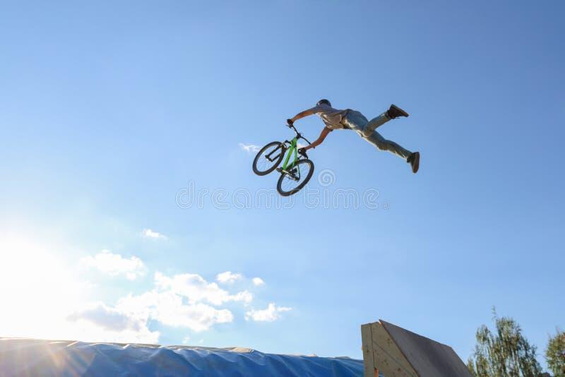 De jonge fietser springt aeromat in het geval van de sprong van het Permanentgebied stock afbeelding