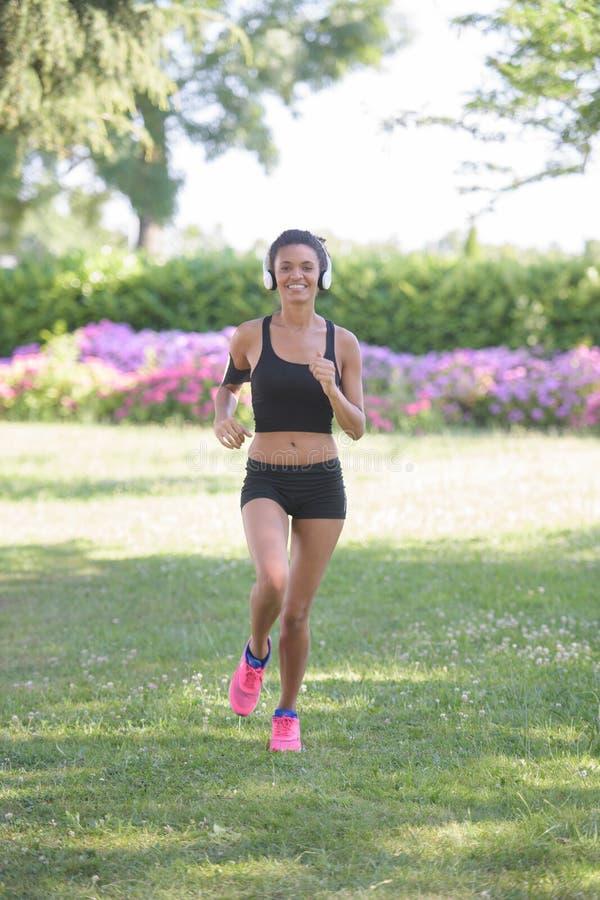 De jonge fitness agent die van de sportenvrouw op parksleep lopen royalty-vrije stock afbeelding