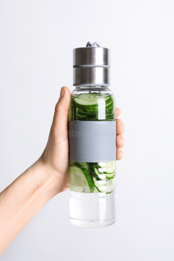 De jonge fles van de vrouwenholding met vers komkommerwater op witte achtergrond stock afbeelding