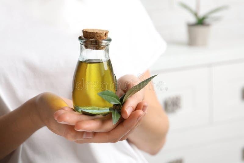 De jonge fles van de vrouwenholding olijfolie, close-up royalty-vrije stock afbeeldingen