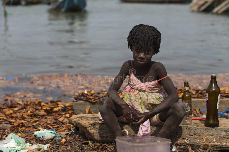 De jonge flessen van de meisjeswas naast het water in de haven van de stad van Cacheu, in Guinea-Bissau royalty-vrije stock foto