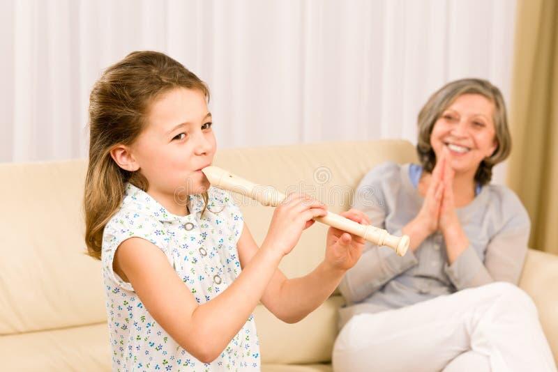 De jonge fluit van het meisjesspel met trotse grootmoeder stock afbeeldingen