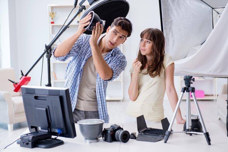 De jonge fotograaf die in fotostudio werken stock afbeeldingen