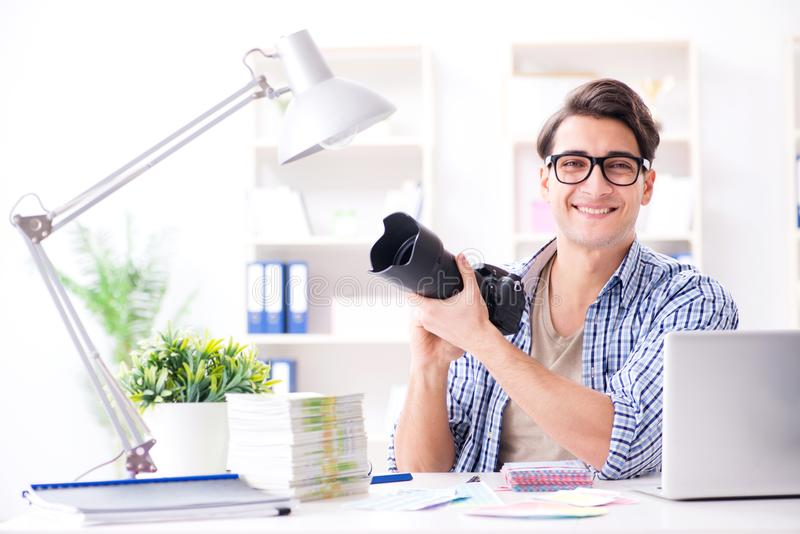 De jonge fotograaf die met zijn camera werken stock afbeeldingen