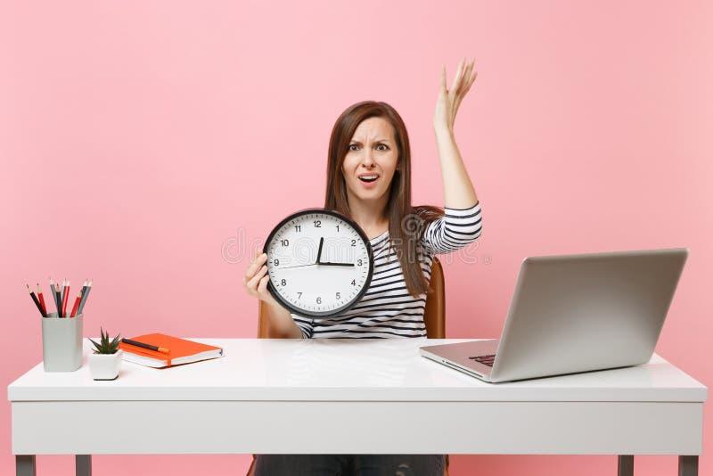 De jonge geïrriteerde vrouw het uitspreiden handen die wekker houden zitten, werken op kantoor met PC-geïsoleerd laptop aan paste stock fotografie