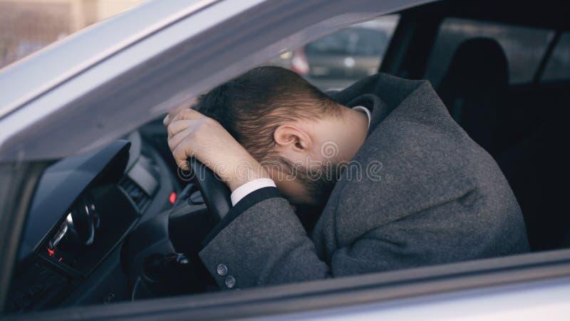 De jonge gebaarde bedrijfsmensenzitting in auto verstoorde zeer en beklemtoonde na zich harde mislukking en het bewegen in opstop stock fotografie