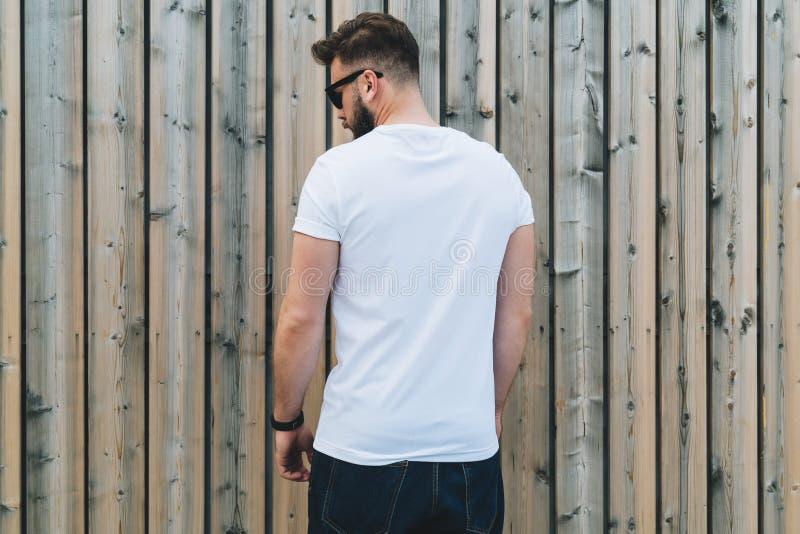 De jonge gebaarde hipstermens gekleed in witte t-shirt en zonnebril is tribunes openlucht tegen houten muur Spot omhoog royalty-vrije stock foto's