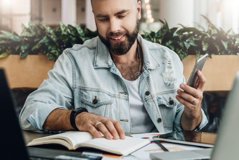 De jonge gebaarde hipstermens zit in koffie voor computers, leest nota's in notitieboekje terwijl het houden van smartphone in ha royalty-vrije stock foto