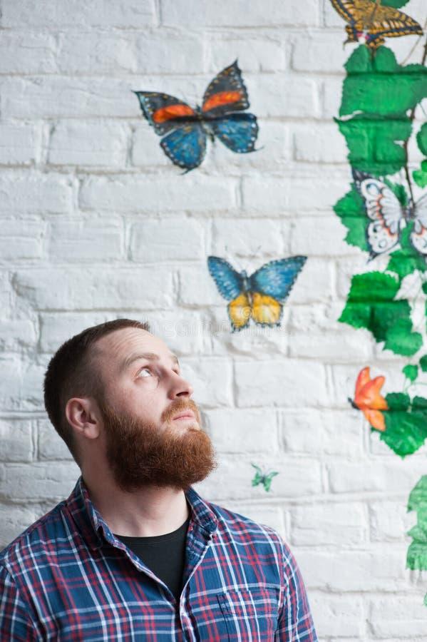 De jonge gebaarde mens bekijkt omhoog graffiti met vlinder royalty-vrije stock foto
