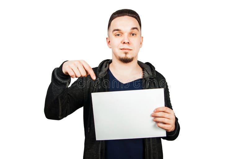 De jonge gebaarde mens kleedde zich in hoodie die leeg document houden exemplaarruimte voor tekst of grafisch ontwerp Ge?soleerdj stock foto