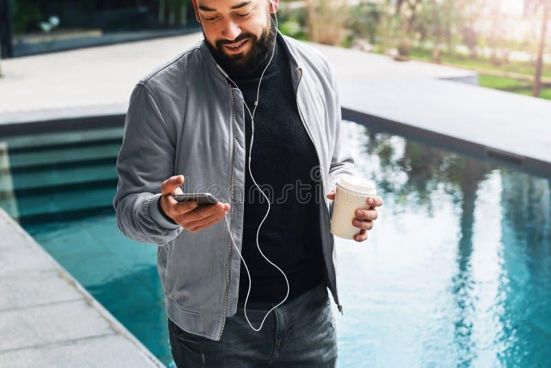 De jonge gebaarde mens luistert aan muziek door hoofdtelefoons op smartphone en drinkt koffie terwijl in openlucht status levenss royalty-vrije stock fotografie