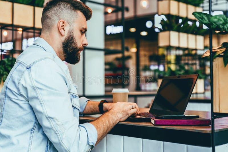De jonge gebaarde mens zit in koffie, typend op laptop De Bloggerwerken in koffiehuis De kerel controleert e-mail op computer stock foto's