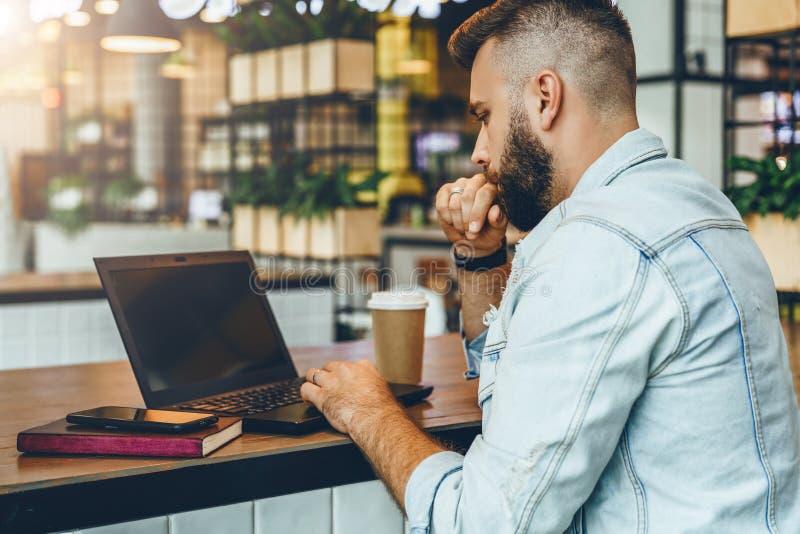 De jonge gebaarde mens zit in koffie, typend op laptop De Bloggerwerken in koffiehuis De kerel controleert e-mail op computer royalty-vrije stock afbeelding