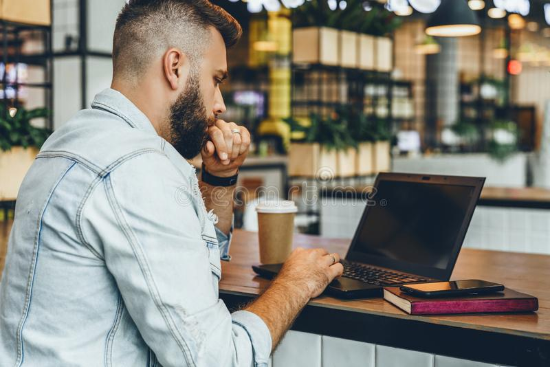 De jonge gebaarde mens zit in koffie, typend op laptop De Bloggerwerken in koffiehuis De kerel controleert e-mail op computer stock foto