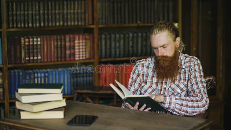 De jonge gebaarde student die in bibliotheek een boek lezen en treft voor examens voorbereidingen royalty-vrije stock afbeelding