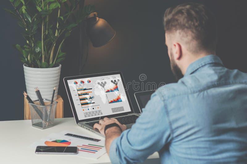 De jonge gebaarde zakenman in denimoverhemd zit in bureau bij lijst en gebruikt laptop met grafieken, grafieken stock foto