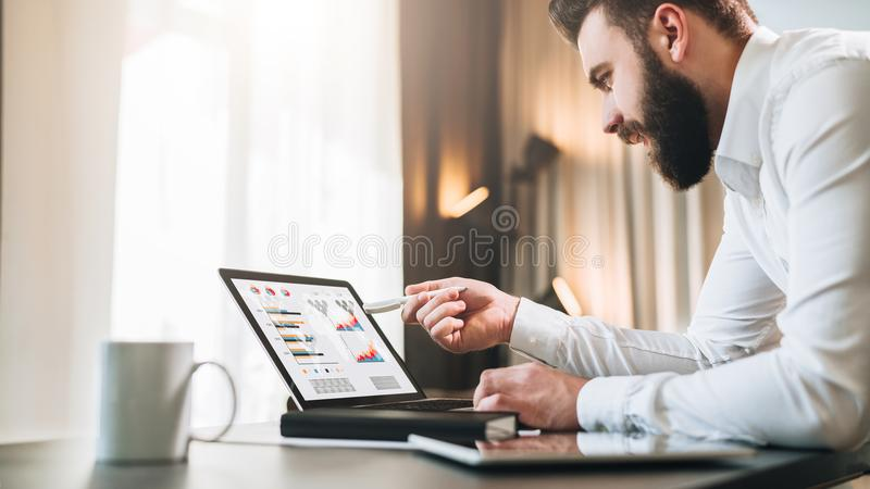 De jonge gebaarde zakenman in wit overhemd zit bij lijst voor computer, die pen op laptop het scherm tonen stock afbeelding