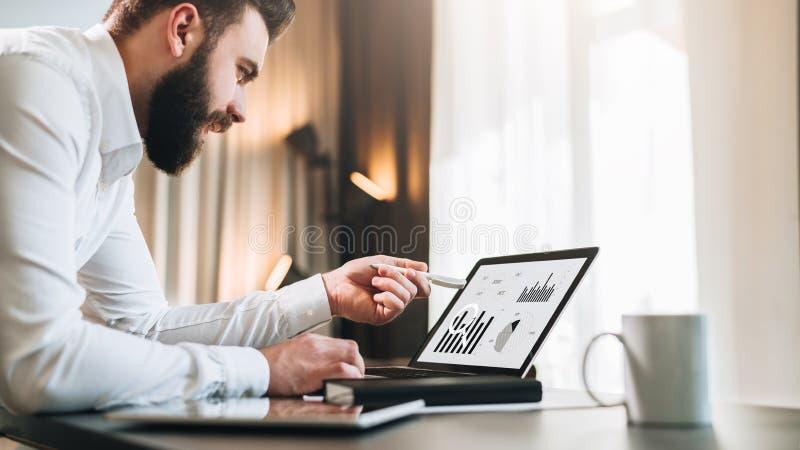 De jonge gebaarde zakenman in wit overhemd zit bij lijst voor computer, richtend met pen op grafieken, grafieken stock foto's