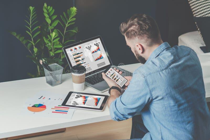 De jonge gebaarde zakenman zit in bureau bij lijst en gebruikt smartphone met grafieken, diagrammen en grafieken op het scherm royalty-vrije stock foto