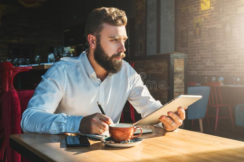 De jonge gebaarde zakenman zit in koffie bij lijst, houdt tabletcomputer en schrijft in notitieboekje royalty-vrije stock foto