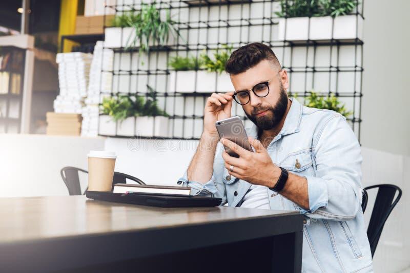 De jonge gebaarde zakenman zit in koffie, gebruikend smartphone Op lijst is gesloten laptop, kop van koffie Het Freelancerwerk stock foto's