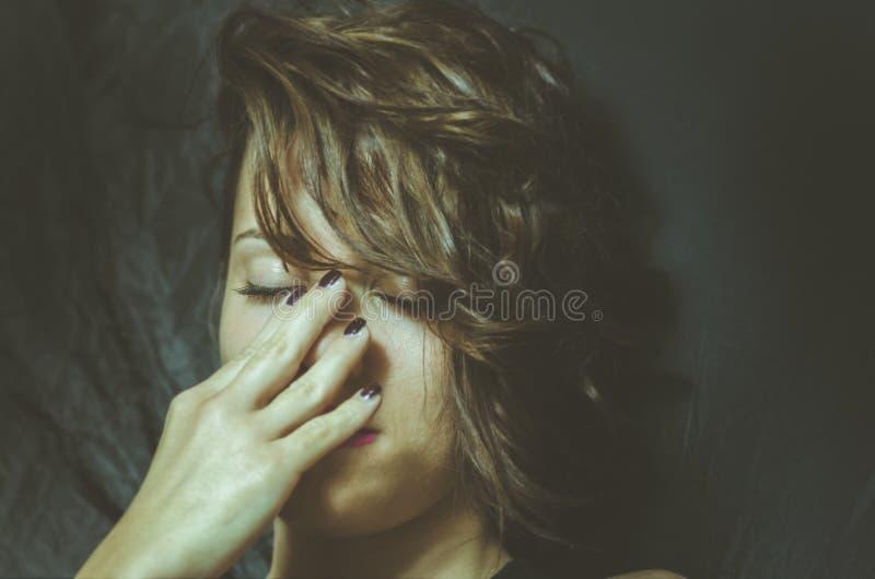 De jonge gedeprimeerde vrouw die miserabele en eenzame dekking voelen haar gezicht met haar dient de donkere ruimte van haar huis stock afbeelding