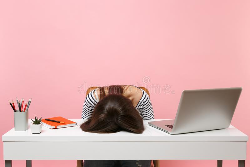 De jonge gefrustreerde uitgeputte vrouw legde haar hoofd op de lijst gaat zitten het werk bij wit bureau met eigentijdse PC-lapto royalty-vrije stock foto's