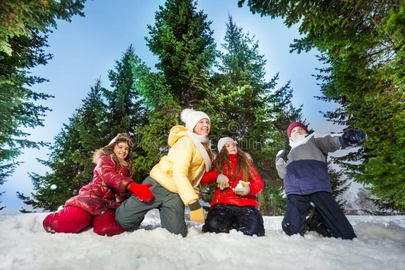 De jonge geitjes concurreert in het werpen van sneeuwballen bij de winterhout royalty-vrije stock fotografie