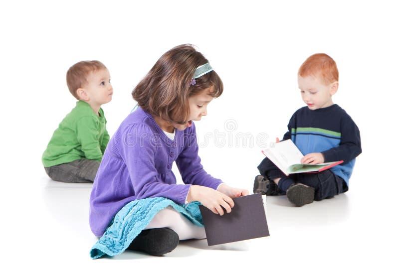 De jonge geitjes die van de zitting boeken lezen royalty-vrije stock afbeeldingen