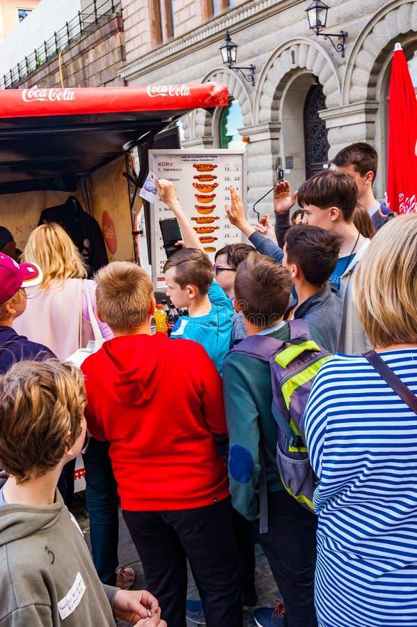 De jonge geitjes die van de toeristenschool zich dichtbij de snel voedselkiosk bevinden, die over wie stemmen hotdog of andere sm royalty-vrije stock foto's