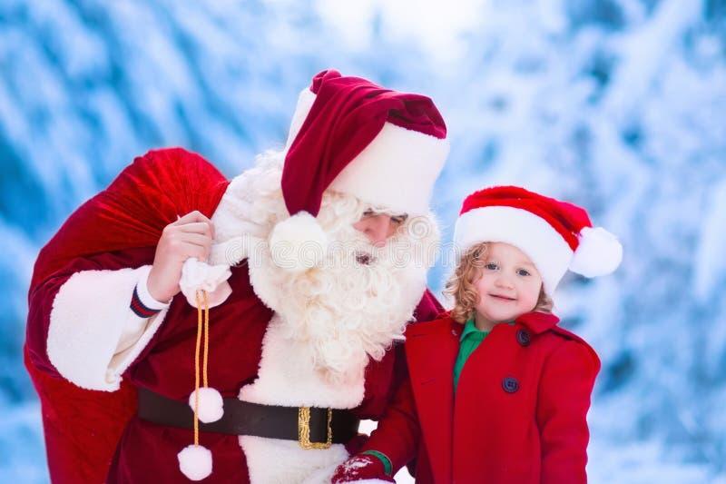 De jonge geitjes en de Kerstman met Kerstmis stellen voor stock fotografie
