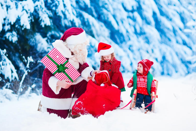 De jonge geitjes en de Kerstman met Kerstmis stellen voor stock afbeeldingen