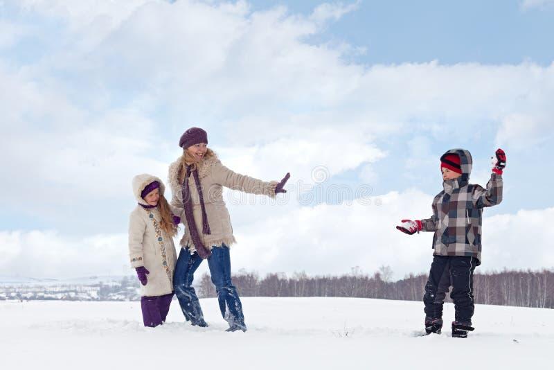 De jonge geitjes en de vrouw genieten van de sneeuw stock foto